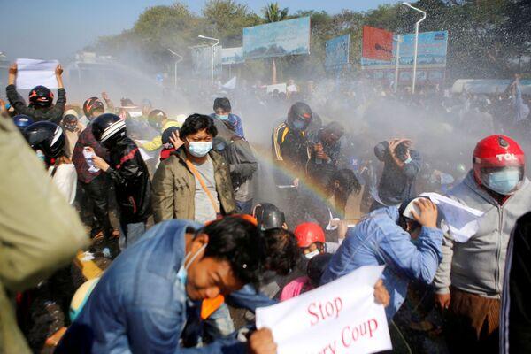 Policie pálila z vodního děla na demonstranty proti převratu v Naypyitae v Myanmaru.  - Sputnik Česká republika