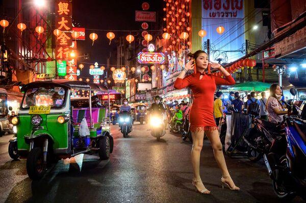 Dívka pózuje pro fotografii na ulici zdobené pro lunární Nový rok, v Bangkoku.  - Sputnik Česká republika