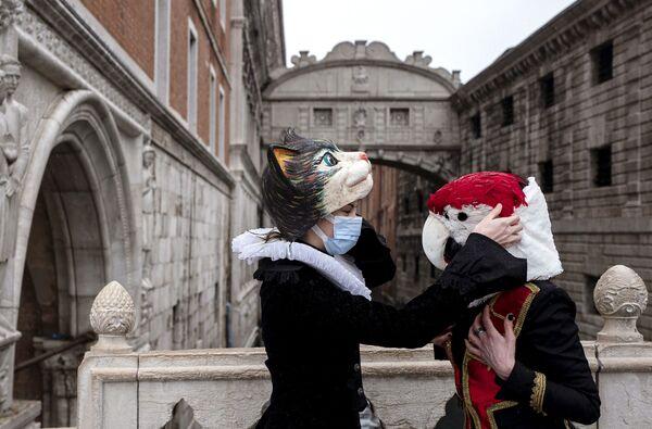 Benátčané v karnevalových maskách a kostýmech na mostě vzdechů v Benátkách.  - Sputnik Česká republika