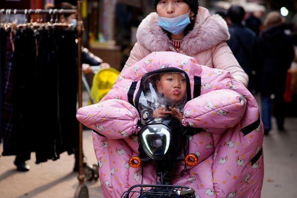 Žena nosí dítě v kočárku na ulici ve Wuchanu.  - Sputnik Česká republika