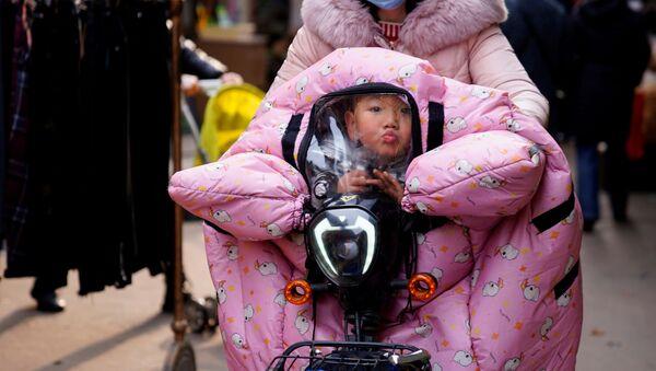 Žena s dítětem v kočárku ve Wu-chanu - Sputnik Česká republika