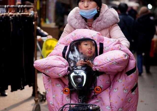 Žena s dítětem v kočárku ve Wu-chanu