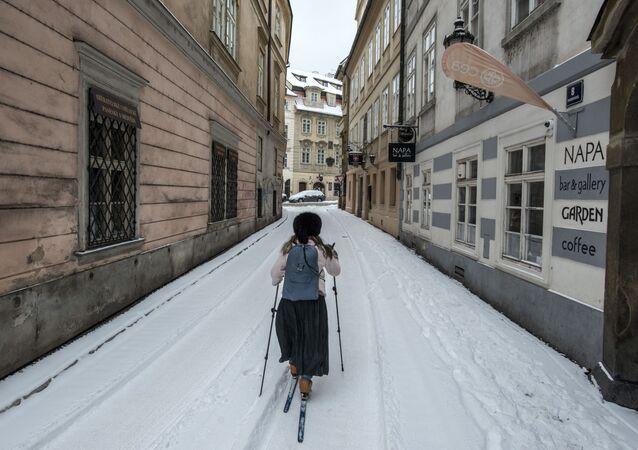 Žena lyžuje v zasněžené Praze