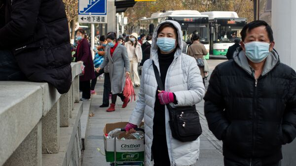 Люди в защитных масках на улице в Ухане, Китай - Sputnik Česká republika