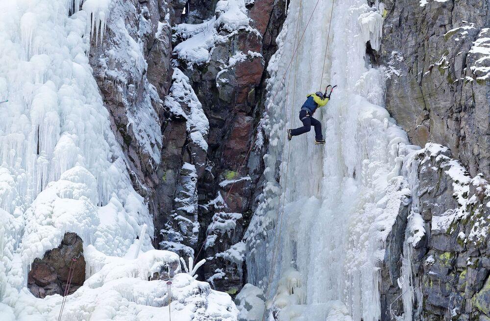 Horolezec během lezení na ledové stěně v Bystřici nad Pernštejnem, Česká republika.