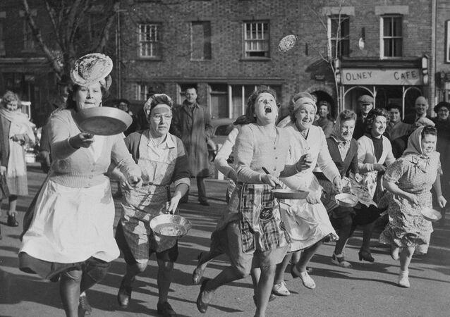 Palačinkové závody ve Velké Británii. Účastníci při nich běží, a zároveň si pohazují palačinkou na pánvi.