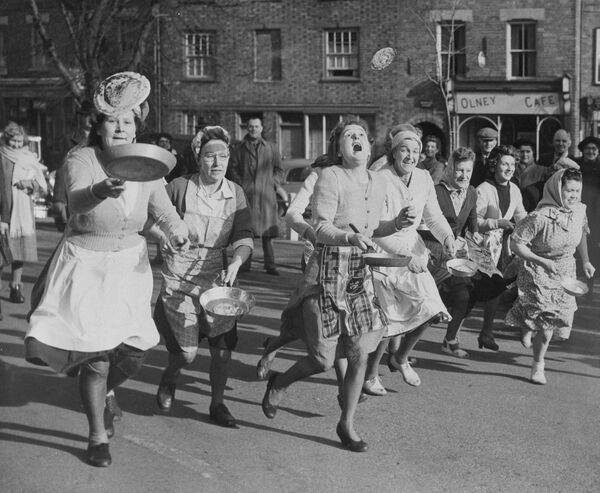 Palačinkové závody ve Velké Británii. Účastníci při nich běží, a zároveň si pohazují palačinkou na pánvi. - Sputnik Česká republika