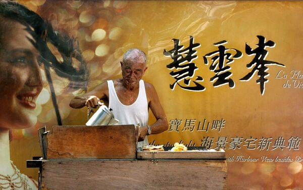 Muž při přípravě palačinek na ulici v Hongkongu. - Sputnik Česká republika