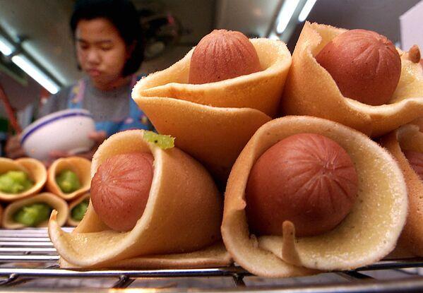 Dívka připravuje mini hot dogy z palačinek a párků v Bangkoku. - Sputnik Česká republika