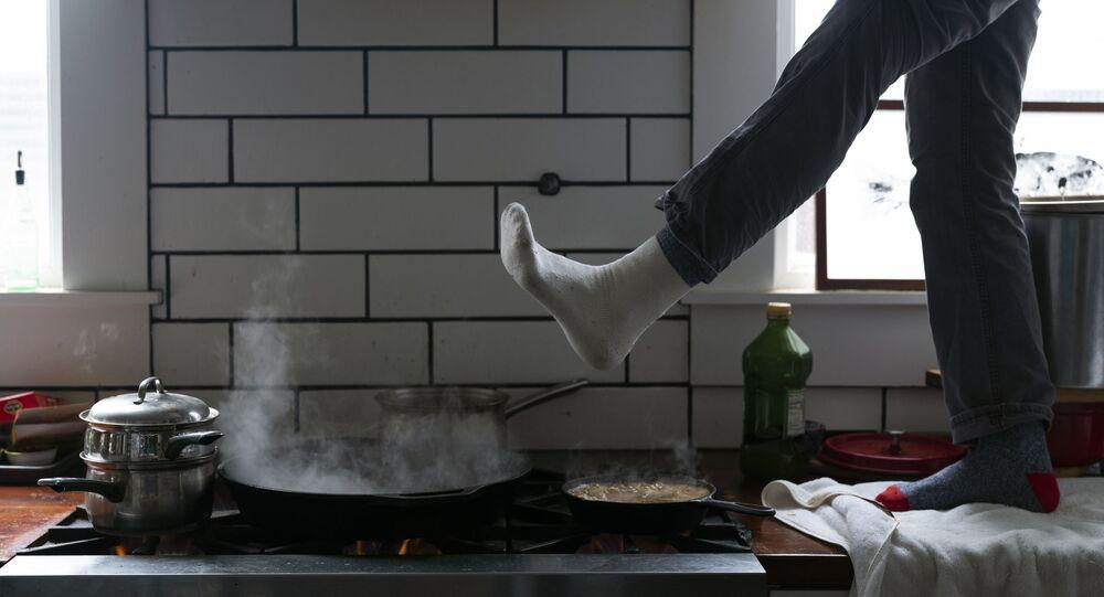 Muž si ohřívá nohy nad plynovým sporákem v Austinu v Texasu v USA