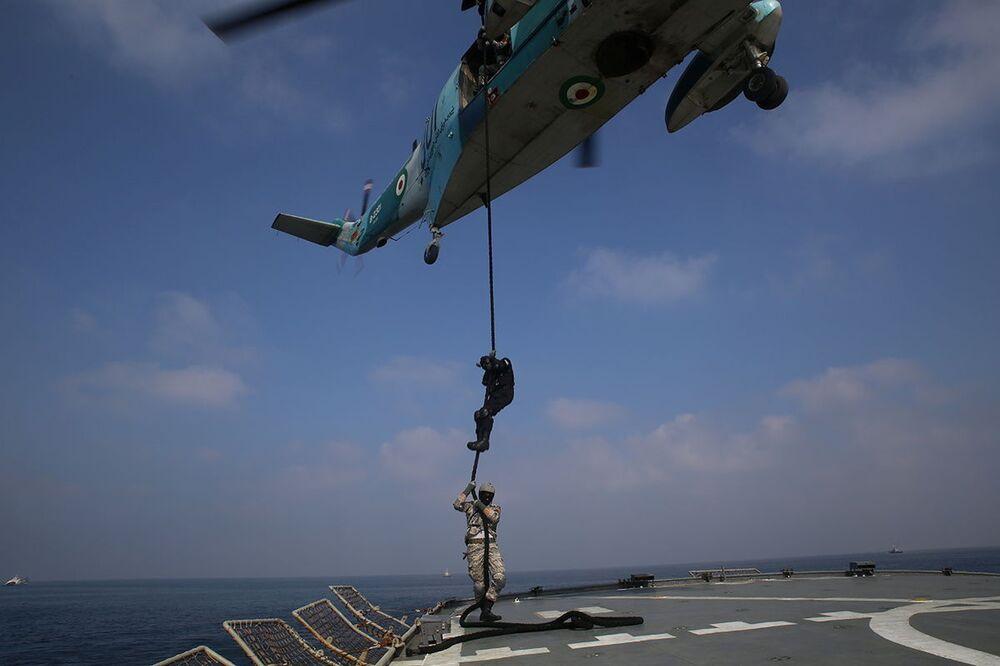 Příslušníci íránského námořnictva sestupují z vrtulníku po laně během společných cvičení Ruska a Íránu.