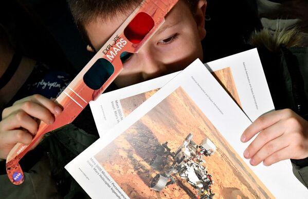 Bosenský chlapec drží 3D brýle a letáky na základní škole ve vesnici Jezero a slaví přistání kosmického roveru Perseverance na Marsu - Sputnik Česká republika