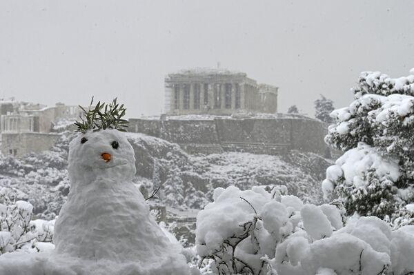 Sněhulák na pozadí zasněženého Parthenónu v Aténách - Sputnik Česká republika