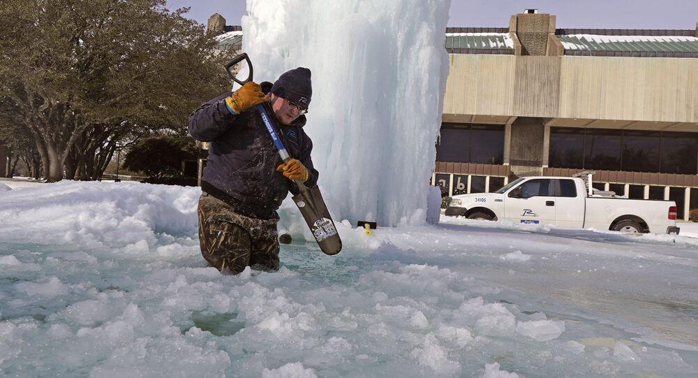 Pracovník láme led ve zmrzlé fontáně v Richardsonu v Texasu v USA