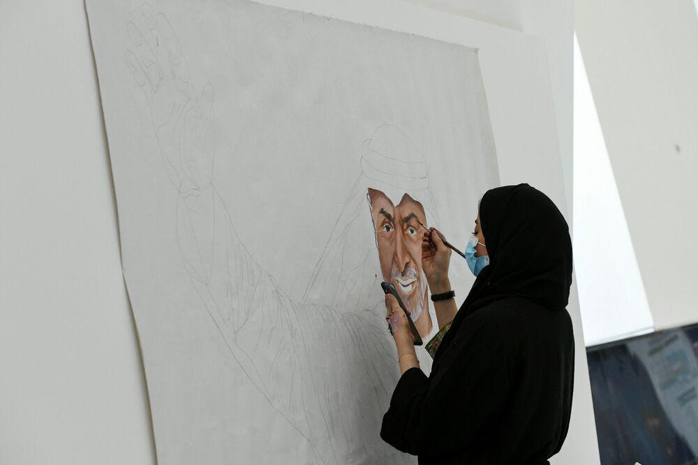Žena maluje portrét korunního prince šejka Mohammeda bin Zayeda al-Nahyanyho