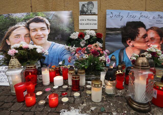 Květiny a svíčky před fotografiemi slovenského novináře Jána Kuciaka, který byl v roce 2018 zastřelen se svou snoubenkou Martinou Kušnirovou