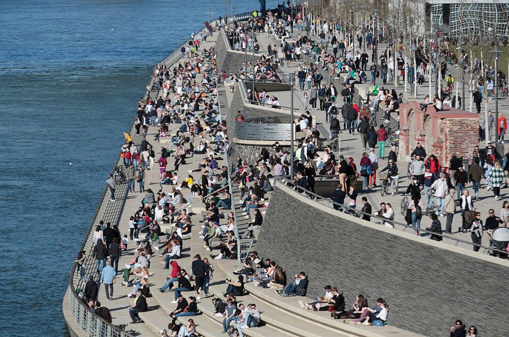 Lidé chytají bronz na břehu řeky v Kolíně nad Rýnem.