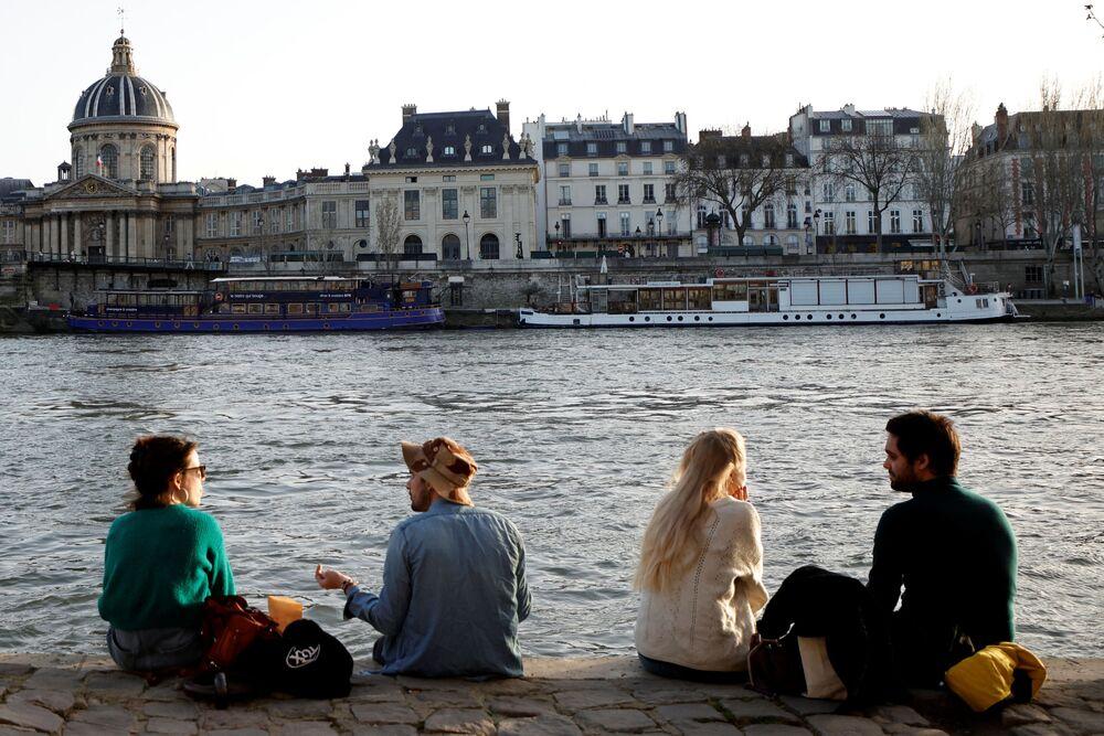 Obyvatelé Paříže si užívají slunečného počasí na břehu řeky Seina v Paříži.