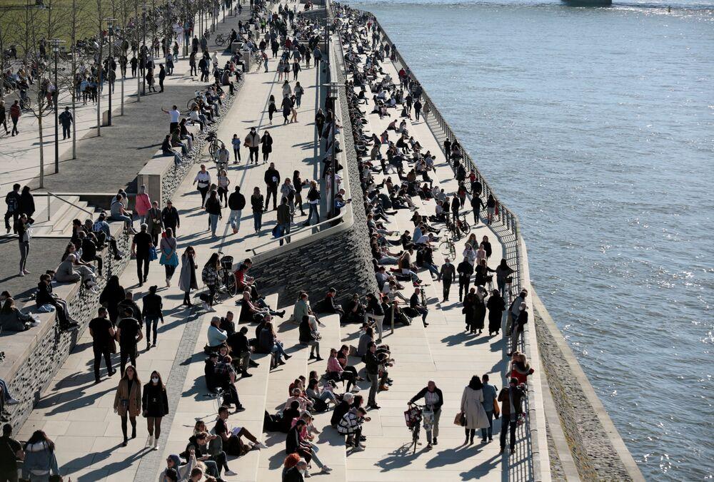 Lidé se procházejí podél břehu řeky v Kolíně nad Rýnem.