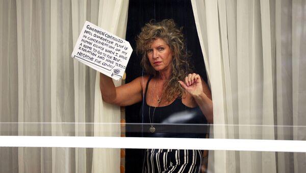 Hotel na letišti Heathrow. Žena drží ceduli, která vyjadřuje její nesouhlas s povinnou karanténou v hotelu, když se může izolovat doma. - Sputnik Česká republika