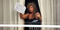 Hotel na letišti Heathrow. Žena drží ceduli, která vyjadřuje její nesouhlas s povinnou karanténou v hotelu, když se může izolovat doma.