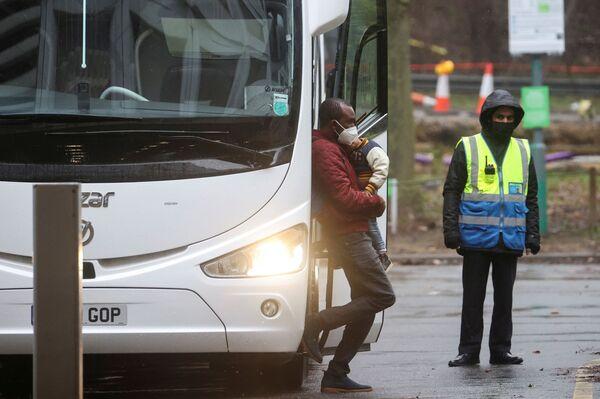 Cestující vystupuje z autobusu, aby nastoupil povinnou karanténu v hotelu Holiday Inn. - Sputnik Česká republika