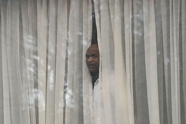 Muž se dívá z okna svého pokoje v hotelu Radisson Blue u letiště Heathrow. - Sputnik Česká republika