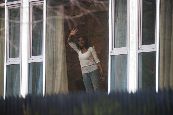 Žena mává z okna svého pokoje v hotelu Radisson Blue u letiště Heathrow. - Sputnik Česká republika