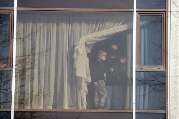 Žena s dítětem se dívá z okna hotelu Radisson Blue u letiště Heathrow. - Sputnik Česká republika