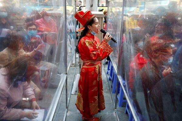 Dívka oblečená jako Bůh bohatství v Hanoji, Vietnam.  - Sputnik Česká republika