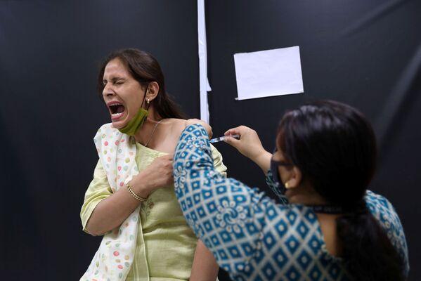 Zaměstnanec indického institutu Serum Institute of India během očkování proti covidu-19 indickou vakcínou CoviShield od společnosti AstraZeneca. - Sputnik Česká republika