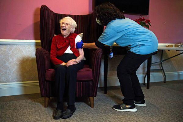 100letý obyvatel pečovatelského domu v Londýně během očkování proti covidu-19 vakcínou Oxford-AstraZeneca. - Sputnik Česká republika