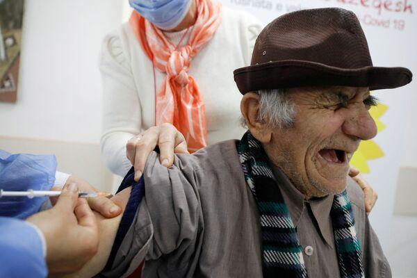 Starší muž během očkování v albánském Fieri            .  - Sputnik Česká republika