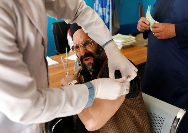 Nemocniční pracovník během očkování AstraZeneca v Kábulu, Afghánistán. - Sputnik Česká republika