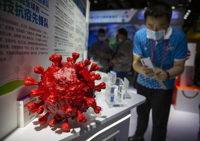 Návštěvník v roušce pořídí fotografii modelu koronaviru a krabiček na vakcíny na covid-19 na stánku čínské farmaceutické firmy Sinopharm na čínském mezinárodním veletrhu obchodu v službách (CIFTIS) v Pekingu