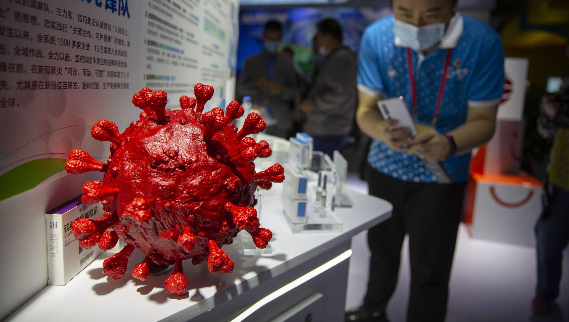 Návštěvník v roušce pořídí fotografii modelu koronaviru a krabiček na vakcíny na covid-19 na stánku čínské farmaceutické firmy Sinopharm na čínském mezinárodním veletrhu obchodu v službách (CIFTIS) v Pekingu - Sputnik Česká republika, 1920, 04.03.2021