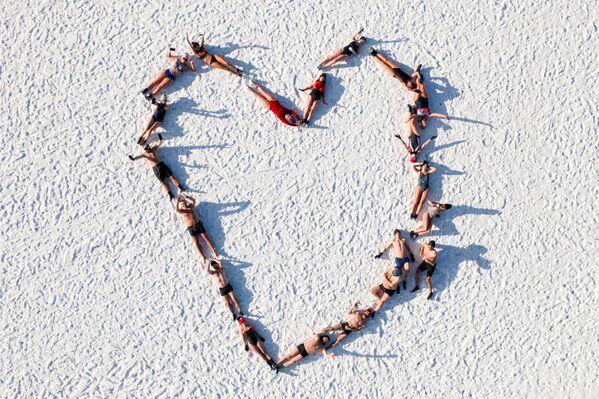 Milovníci zimního koupání leží na pláži Baltského moře.  - Sputnik Česká republika