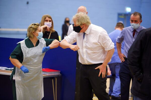 Britský premiér Boris Johnson se zdravotní sestrou během návštěvy očkovacího centra proti koronaviru v Cwmbrânu.  - Sputnik Česká republika