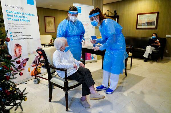 Zaměstnankyně pečovatelského ústavu s pacientem před očkováním ve španělském Madridu - Sputnik Česká republika