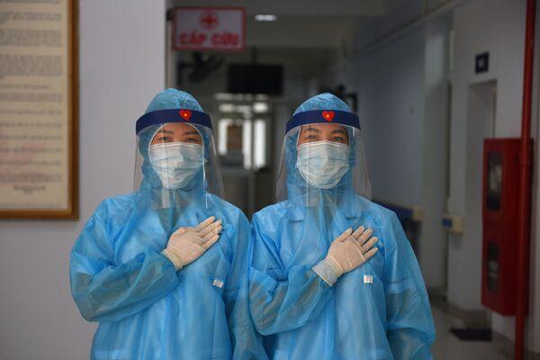 Zdravotníci v ochranném oděvu v dočasném centru testování na koronavirus v Hanoji ve Vietnamu - Sputnik Česká republika