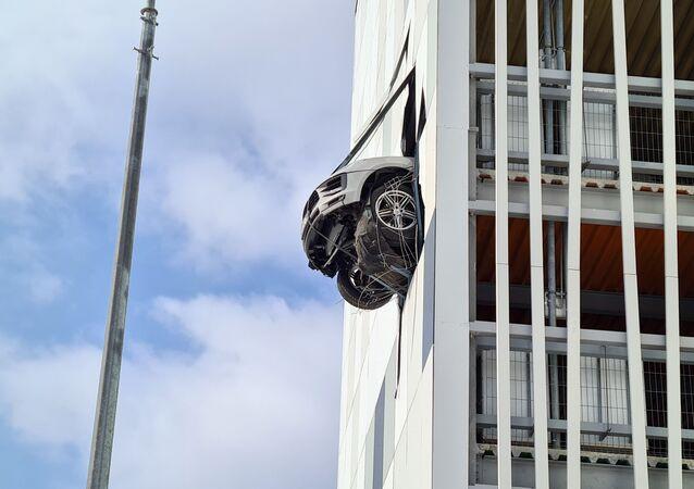 Řidič Porsche prorazil zeď vnitřního parkoviště a k jeho smůle v ní uvízl
