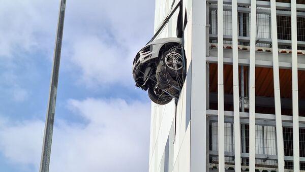 Řidič Porsche prorazil zeď vnitřního parkoviště a k jeho smůle v ní uvízl - Sputnik Česká republika