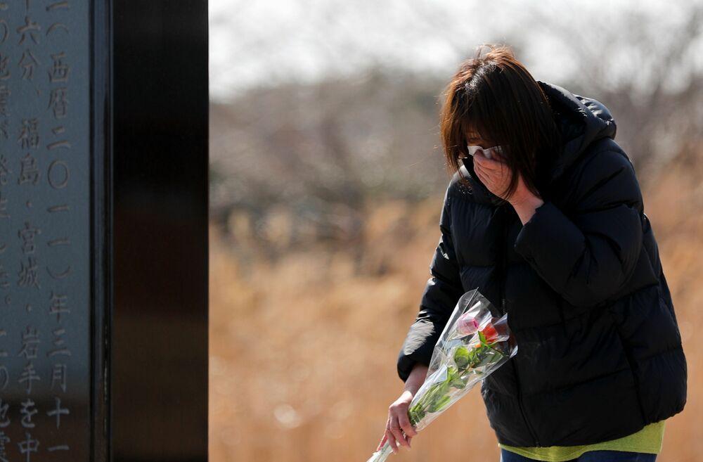 Žena klade květiny k památníku obětí zemětřesení r. 2011