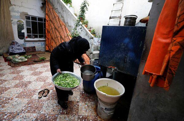 Sedmatřicetiletá vdova proplachuje salát v syrském městě Dúmá.  - Sputnik Česká republika
