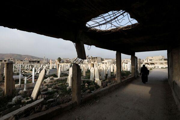 Žena se prochází po hřbitově v syrském městě Dúmá. - Sputnik Česká republika