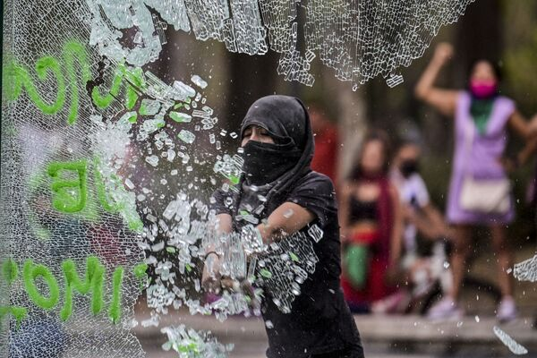 Žena rozbijí sklo během demonstrace na počest Mezinárodního dne žen v Mexiku.  - Sputnik Česká republika
