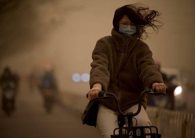 Dívka během písečné bouře v Pekingu