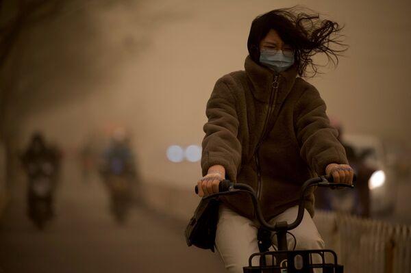 Dívka během písečné bouře v Pekingu.  - Sputnik Česká republika