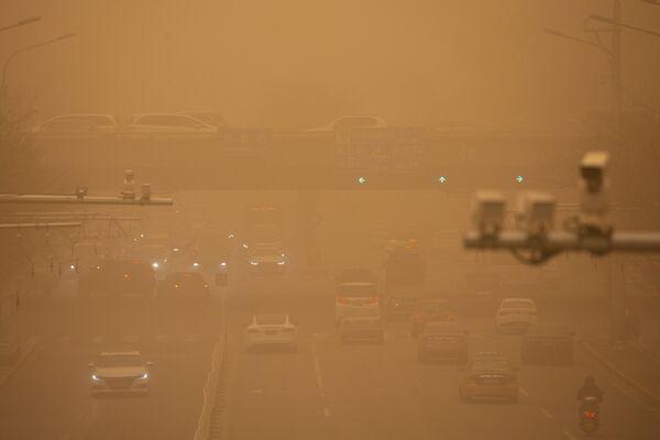 Auta na ulici během písečné bouře v Pekingu.  - Sputnik Česká republika