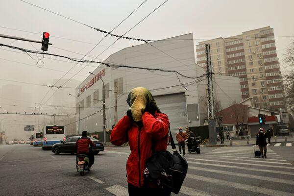 Dívka během mlhy po písečné bouři v Pekingu.  - Sputnik Česká republika